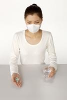 薬とコップの水を持つマスクの女性