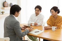 ビジネスマンの説明を聞く日本人夫婦