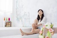 壁によりかかって座る日本人女性