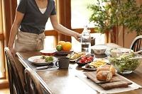 ダイニングテーブルに料理を運ぶ女性