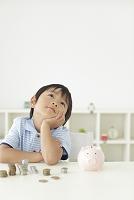 貯金箱の前で悩む日本人の男の子