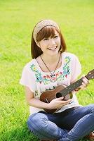 芝生の上でウクレレを弾く女性