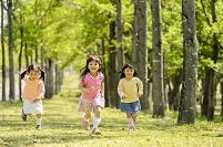 新緑の公園で走る日本人の子供