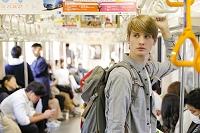 電車を乗る若い外国人男性