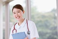 廊下を歩く笑顔の若い日本人女性看護師