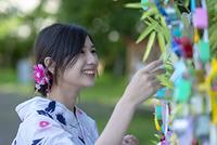 七夕の飾りを見る浴衣の日本人女性