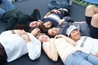 トランポリンの上に寝る若者達
