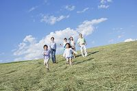 丘を駆け下りる3世代の日本人親子