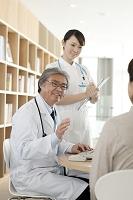 診察室で患者の診察をする医者と看護師
