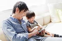 ソファに座ってタブレットを見る日本人親子