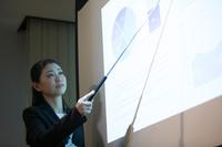 会議で説明をする日本人ビジネスウーマン