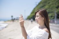 ビーチサイドで音楽を聴く日本人女性