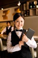 メニューを持っている笑顔の日本人女性従業員