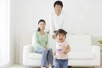 リビングで遊ぶ小さな女の子と両親