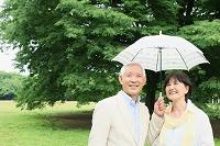 日傘をさすシニア夫婦