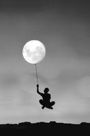 月を持って浮かぶ男