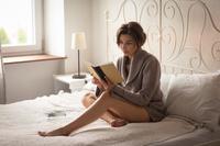 寝室で本を読む外国人女性