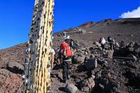 富士山九合目付近の柱に刺された硬貨と登山者