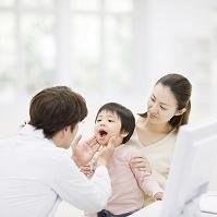 母の膝に座り医者に診察を受ける日本人の子供