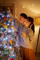 クリスマスツリーに飾り付けをする日本人カップル