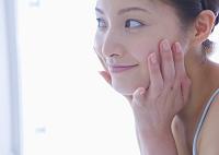 鏡を見てフェイスケアをする日本人女性