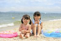 砂浜に並んで座る日本人の女の子