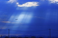 雲間から差し込む光の中を飛ぶ飛行機