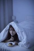 布団に隠れてドーナツを食べる日本人女性