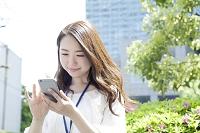 スマートフォンを使う20代日本人女性ビジネスイメージ