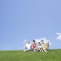 草原に座る日本人家族と犬