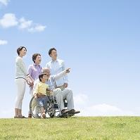 車椅子に乗る男性と日本人家族