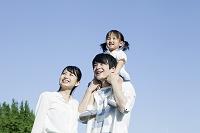 肩車をする20代の若い夫婦と子供