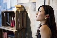 本棚の横に座る日本人女性