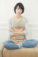 ソファの上で胡座をかく20代日本人女性