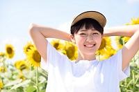ヒマワリ畑で帽子を手にやる笑顔の日本人女性