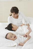 白い布団で眠るお母さんと赤ちゃんと女の子