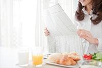 新聞を読んでいる出勤前の女性