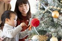 クリスマスツリーの飾り付けをする日本人親子