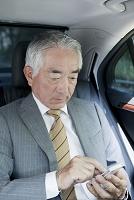 スマートフォンを操作する社内の中高年日本人ビジネスマン