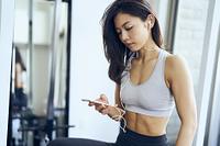 トレーニング中にスマートフォンで音楽を聴く日本人女性
