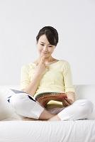 ソファに胡坐をかいて本を読む女性