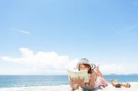 砂浜の上に寝転がって読書する日本人女性