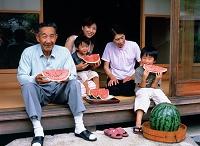 縁側でスイカを食べる三世代