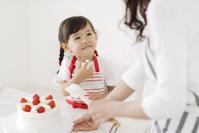 お母さんとケーキを作る小さな女の子