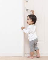ドアノブを掴んで振り返る日本人の男の子
