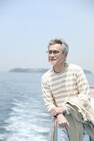 フェリーのデッキで海を見る中年男性