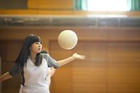 体育館でバレーボールをする女子学生