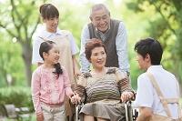 車いすに座るシニア女性と孫とシニア男性と介護士