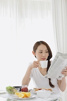 朝食をとりながら新聞を読む日本人女性