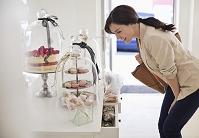並べられた店頭のお菓子を眺める外国人女性